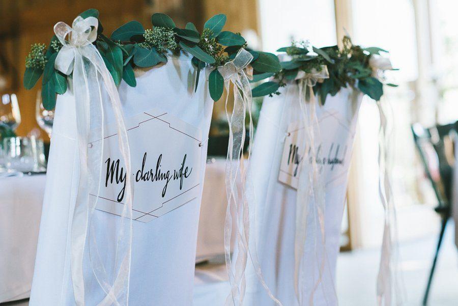 Dekoration an den Stühlen des Brautpaares: Heiraten in der Scheune