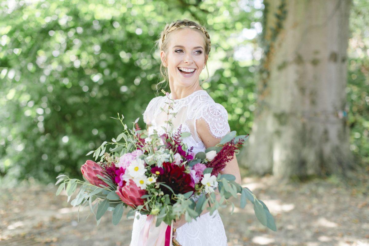 Lachende Braut mit üppigem Brautstrauß