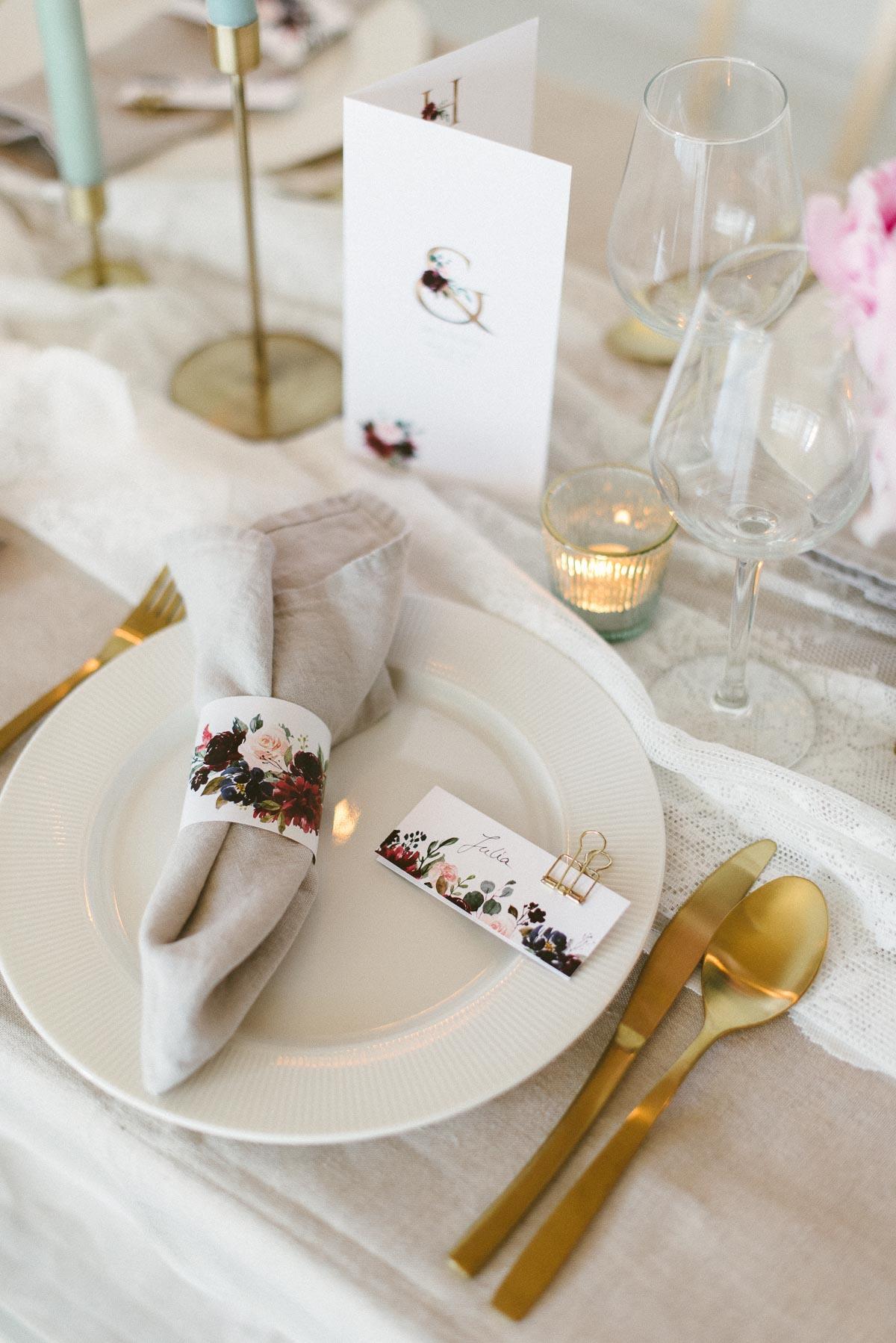 Gedeckter Tisch mit Pfingstrosen und goldenem Besteck