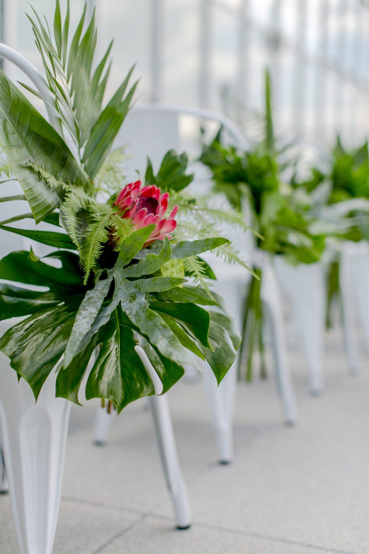 Monstera Blätter: Dekoration der Sitzplätze der Gäste bei der Trauung