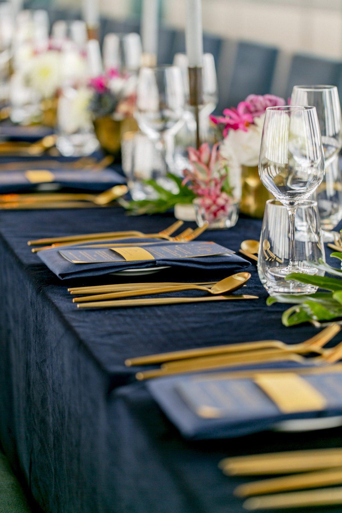 Eingedeckter Tisch mit dunkelblauer Tischdecke und goldenem Besteck