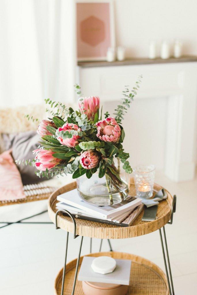 So arrangiert man einen Protea Strauß mit Eukalyptus in einer großen Glasvase.