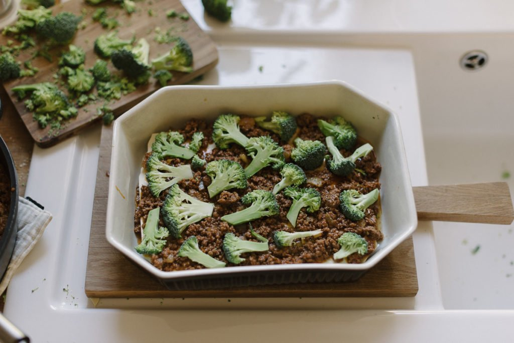 Brokkoli auf der Lasagne verteilen