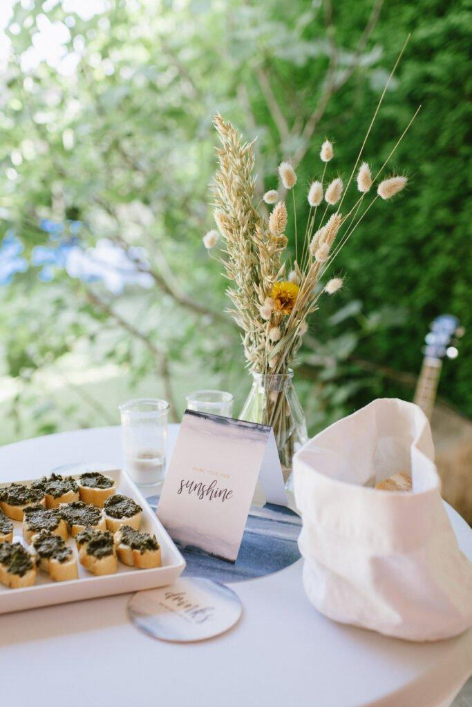 Dekoration auf dem Stehtisch mit Gräsern und Fingerfood