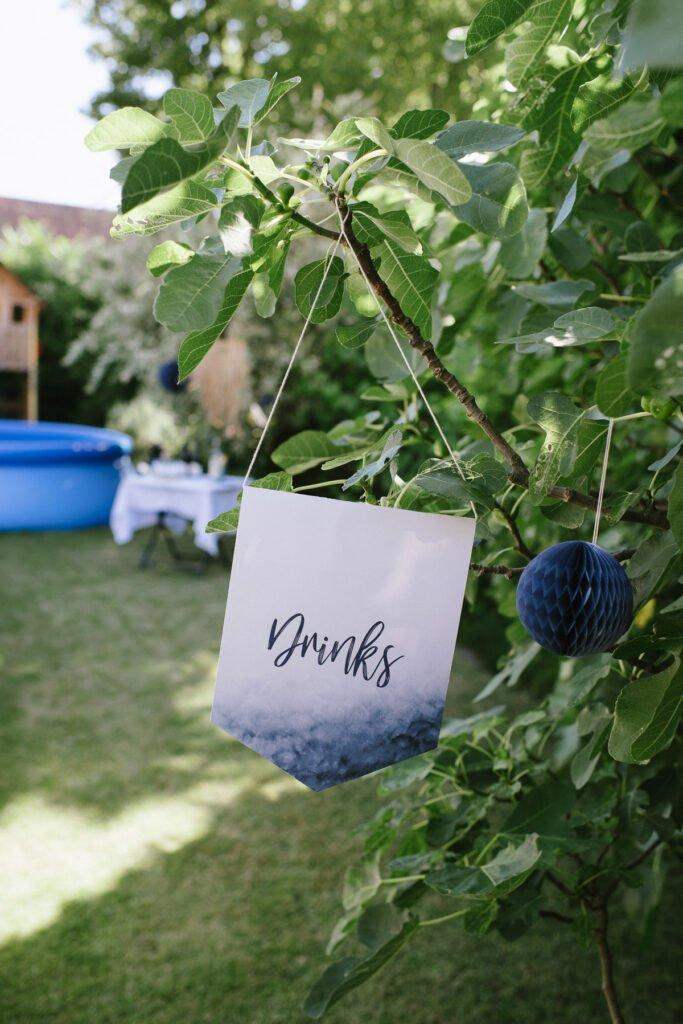 Wimpel mit Aufdruck 'Drinks' hängt am Feigenbaum