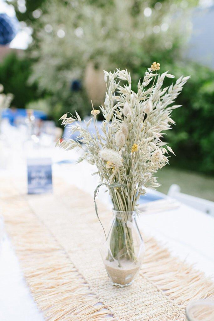 Kleinere Blumenvase mit getrockneten Gräsern auf dem Tisch