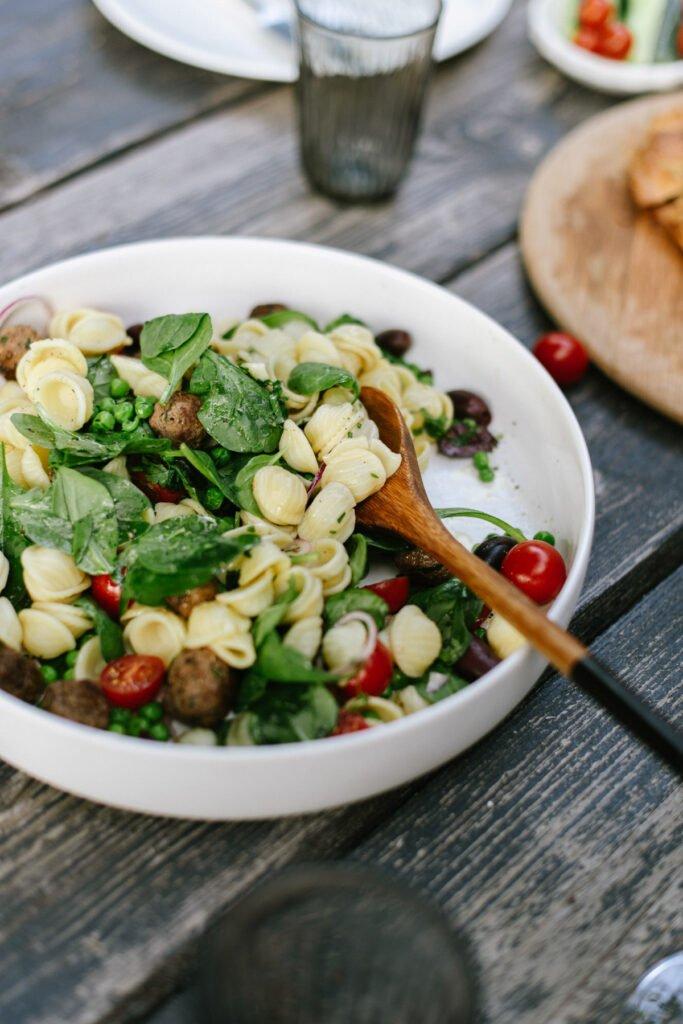 Lecker frischer Nudelsalat mit Spinat, Erbsen und Fleischbällchen