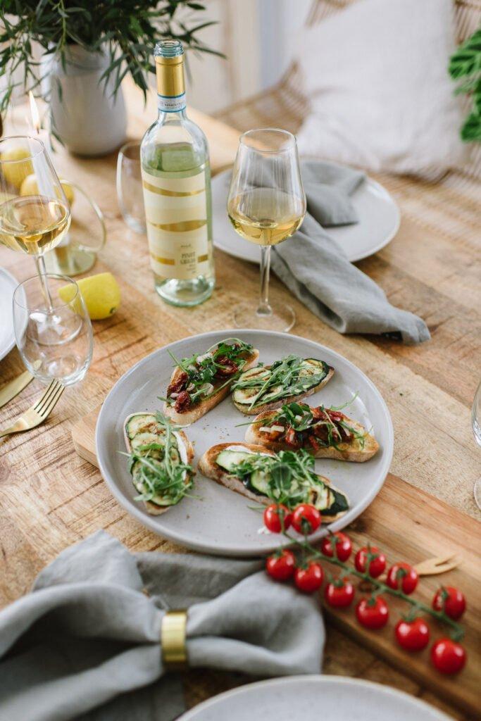 Bruschetta auf einem Teller, Weinglas und Weinflasche im Hintergrund