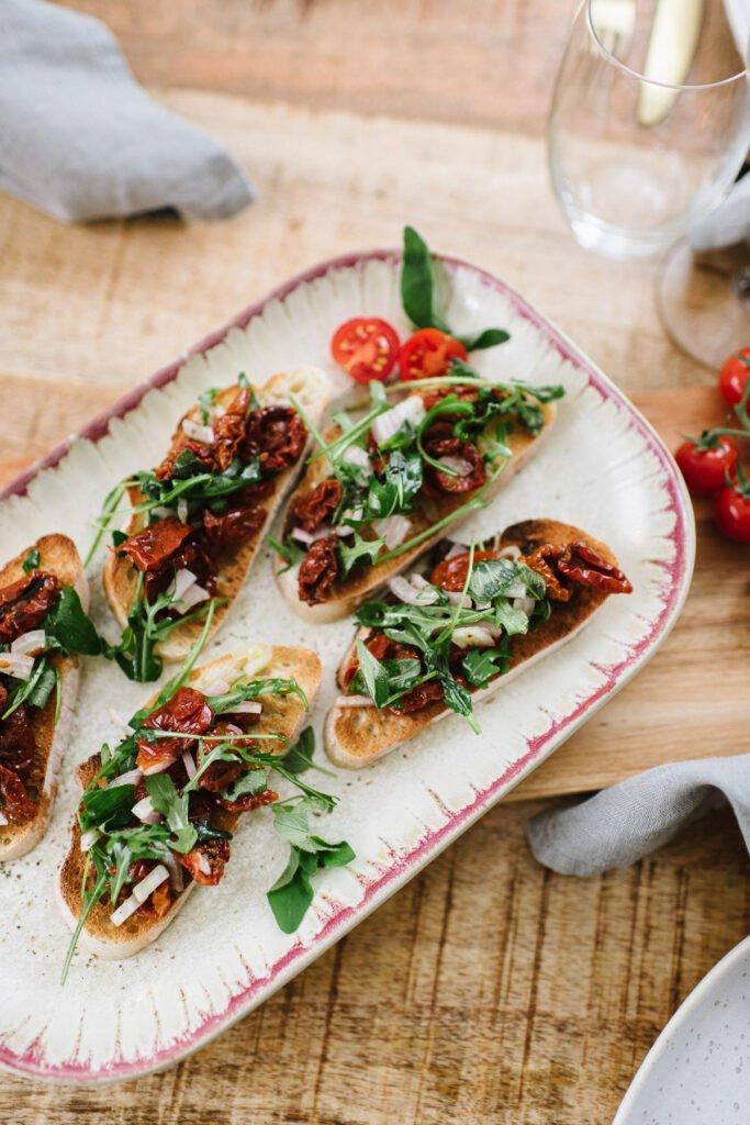 Vegetarische Bruschetta mit getrockneten Tomaten und Oragano auf einer Platte angerichtet.