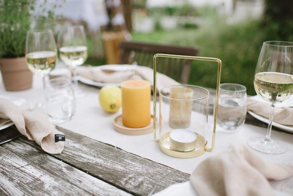 Gedeckter Tisch mit Laternen, Stumpenkerzen und Naturmaterialien