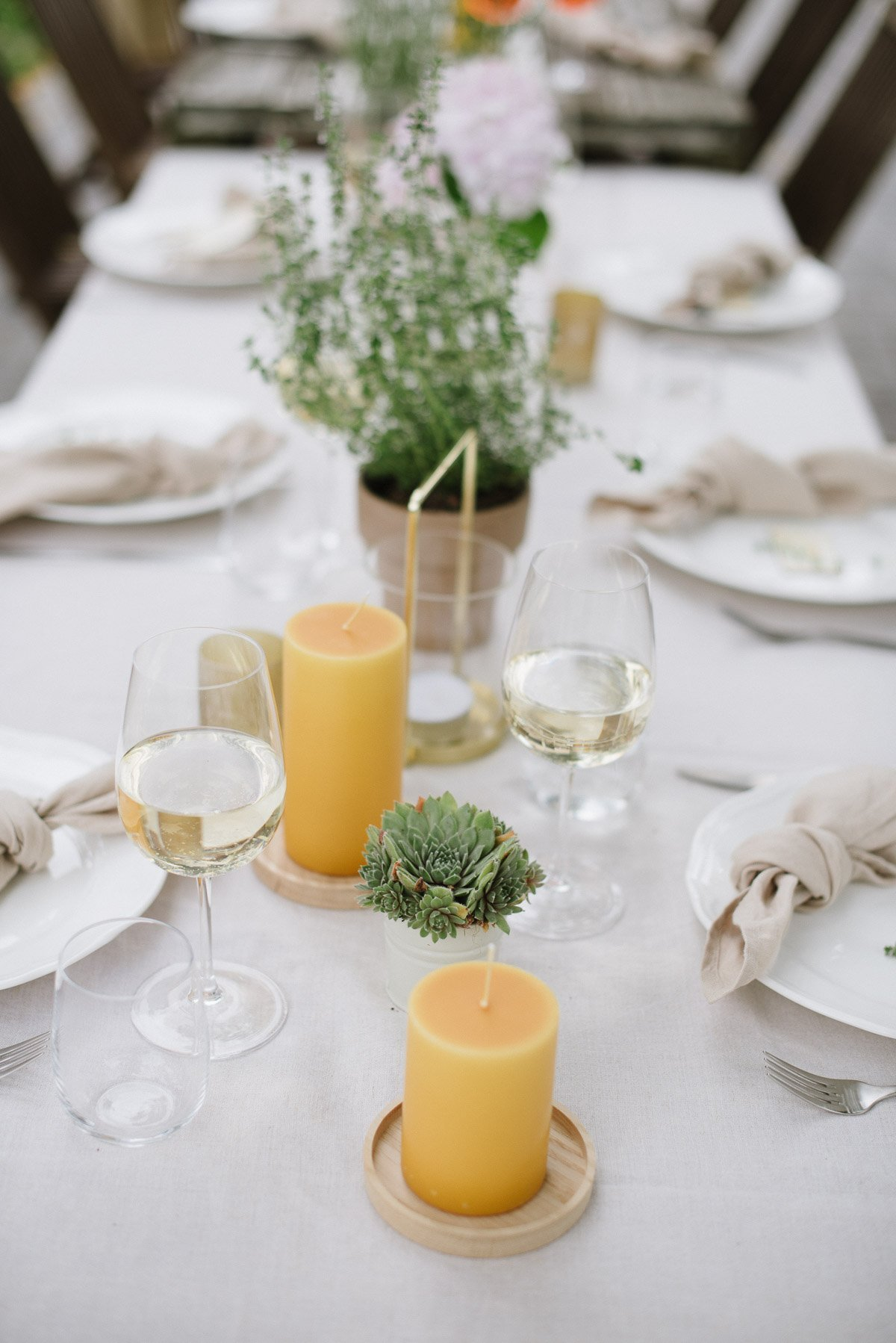 Gedeckter Tisch mit gelben Stumpenkerzen zu Gartenparty zum 40. Geburtstag
