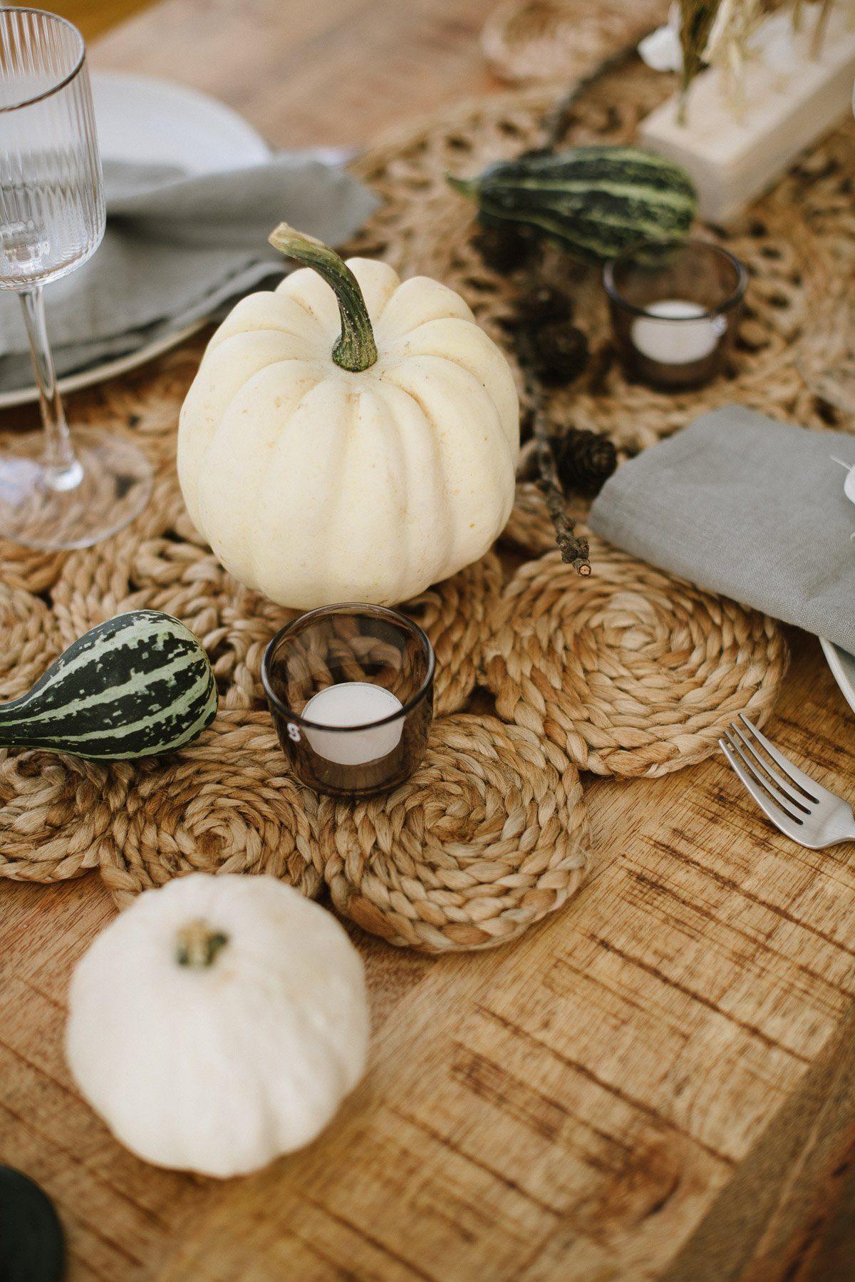 Herbsttisch gedeckt mit weißen und grünen Kürbissen