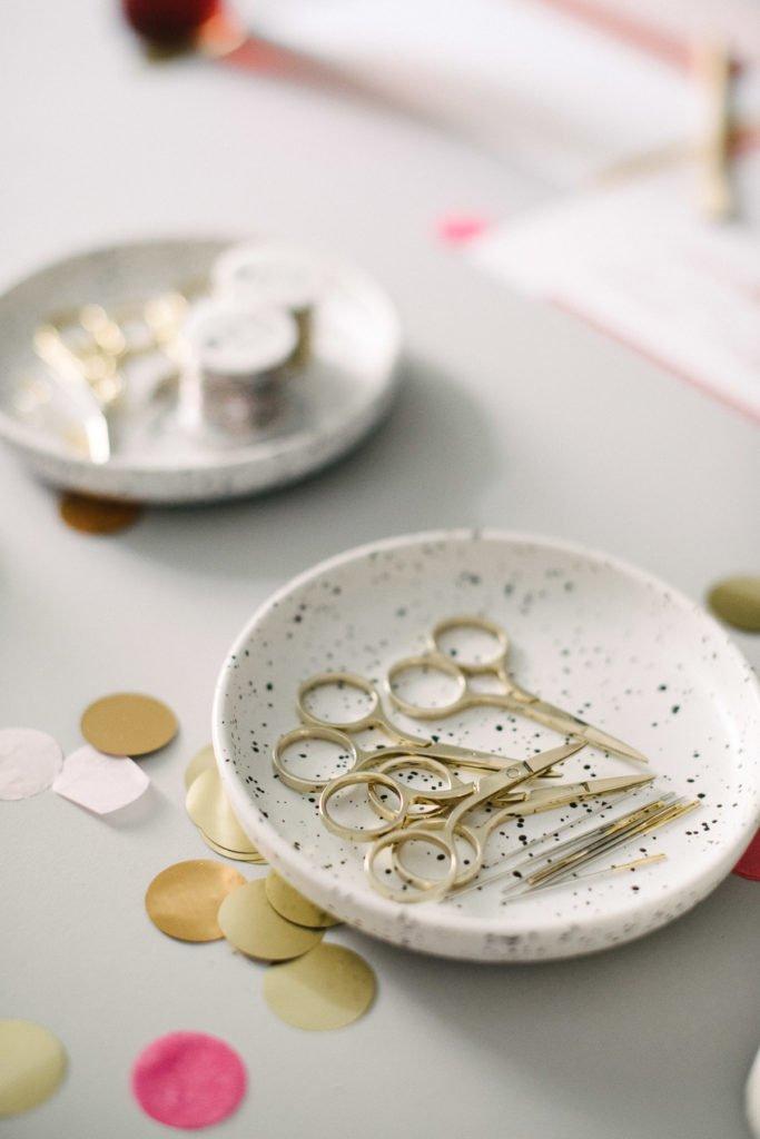 Teller mit kleinen, goldenen Scheren