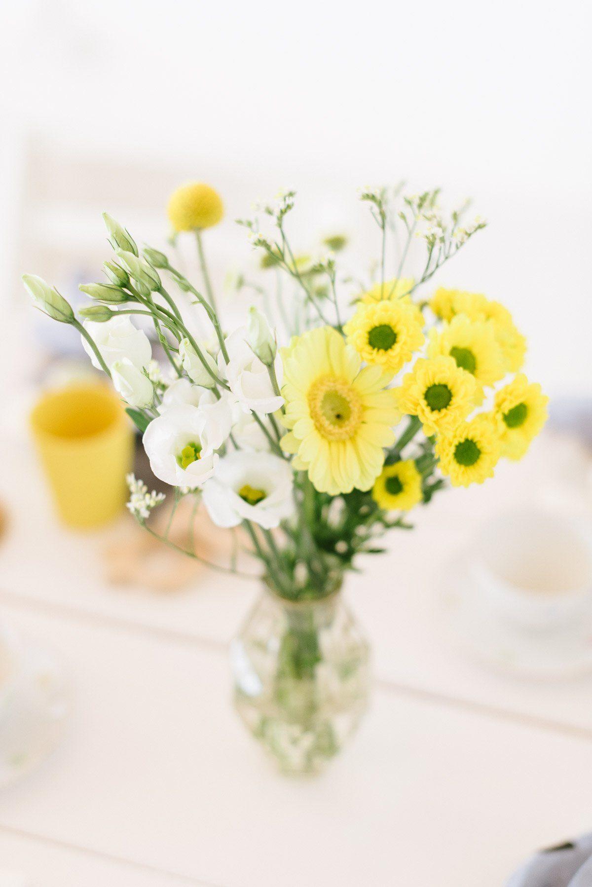gelbe Blumensträuße in kleinen Vasen