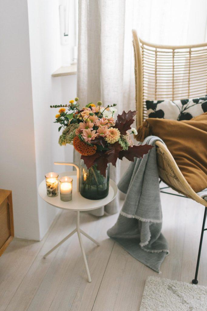 Sessel aus Ratten mit sanftem Herbstblumenstrauß