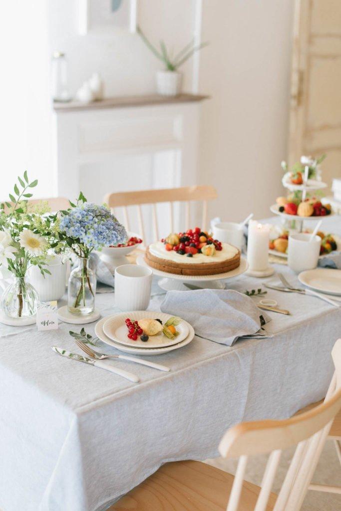 Brunch am Tisch mit hellblauer Leinentischdecke