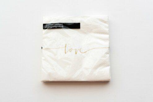 Papierserviette mit dem goldenen Aufdruck 'Love'